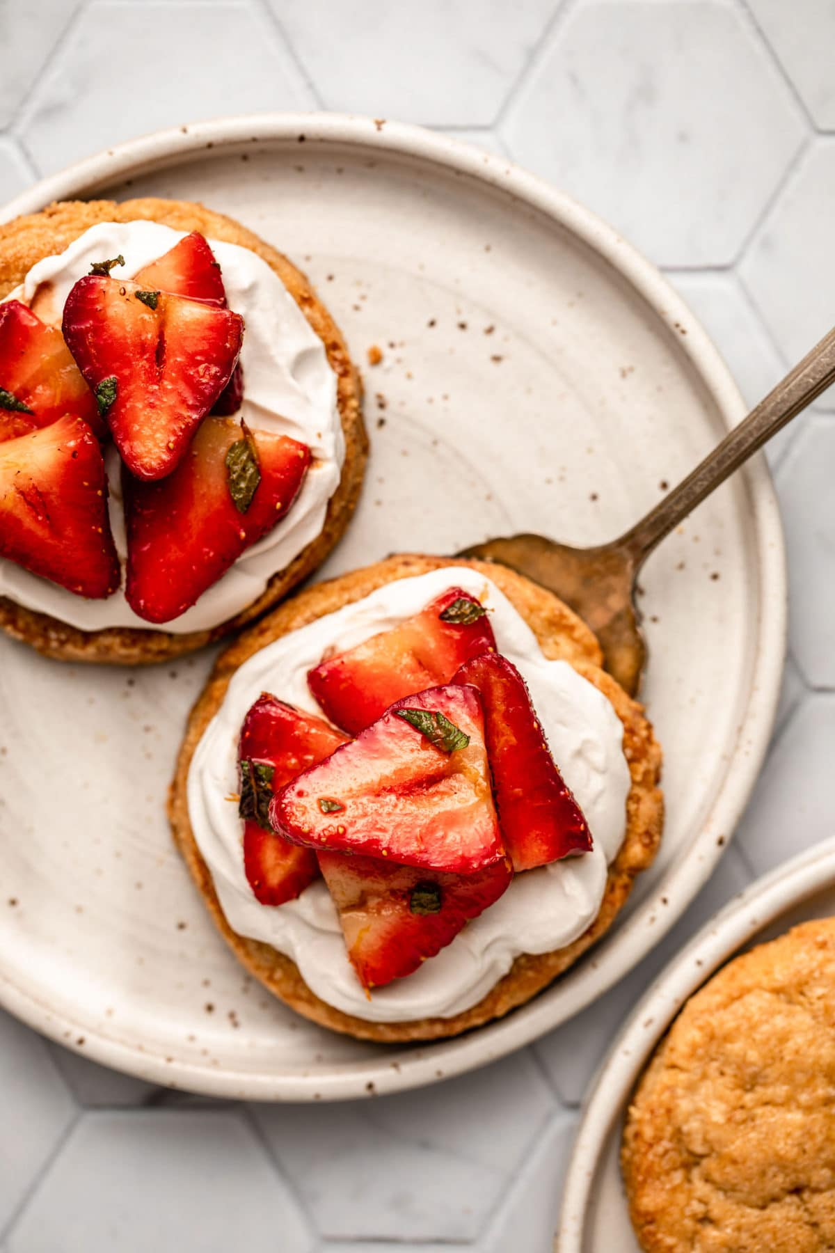 two strawberry shortcakes topped with coconut cream and strawberries on white speckled plate on tiled background