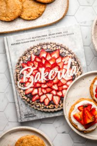 bakerita cookbook on tile background with strawberry shortcakes on white plate