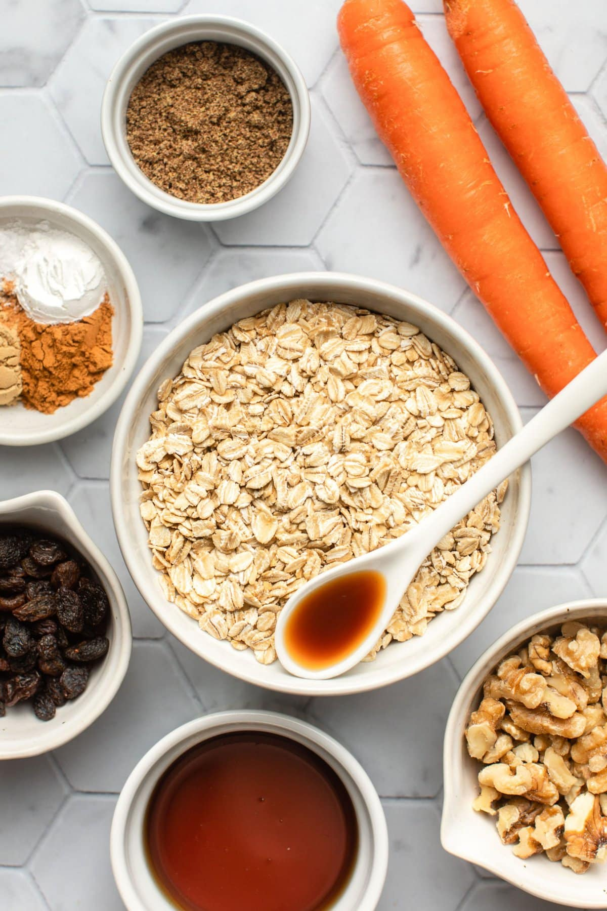 ingredients for carrot cake oatmeal in white bowls on tile background