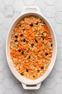 dish of carrot cake oatmeal before baking on tile background