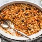 white dish of baked carrot cake oatmeal with gray towel on tile background