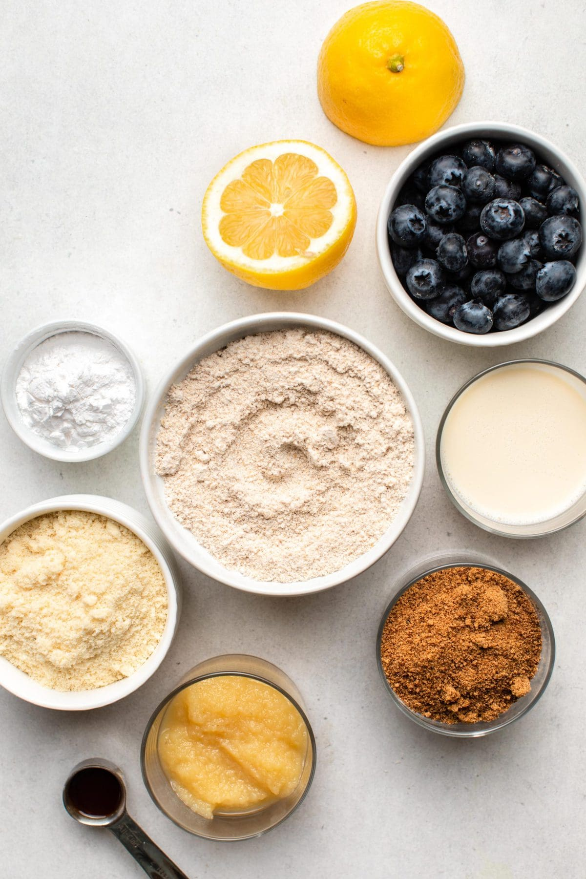 ingredients for lemon blueberry muffins in small bowls on grey background