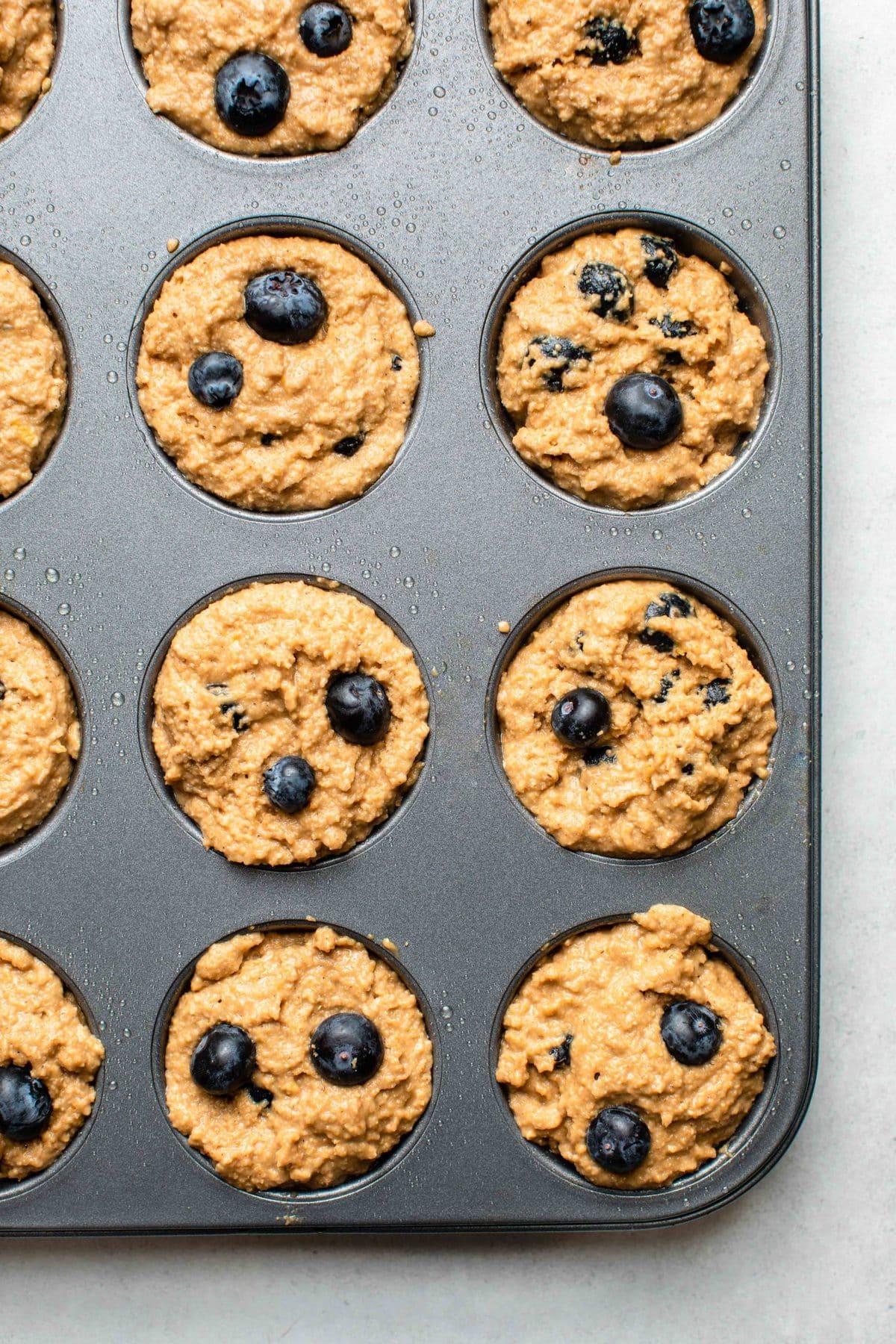 lemon blueberry muffin batter in muffin tin before baking