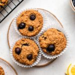 3 lemon blueberry muffins on white plate with bowl of blueberries and lemon slices on white background