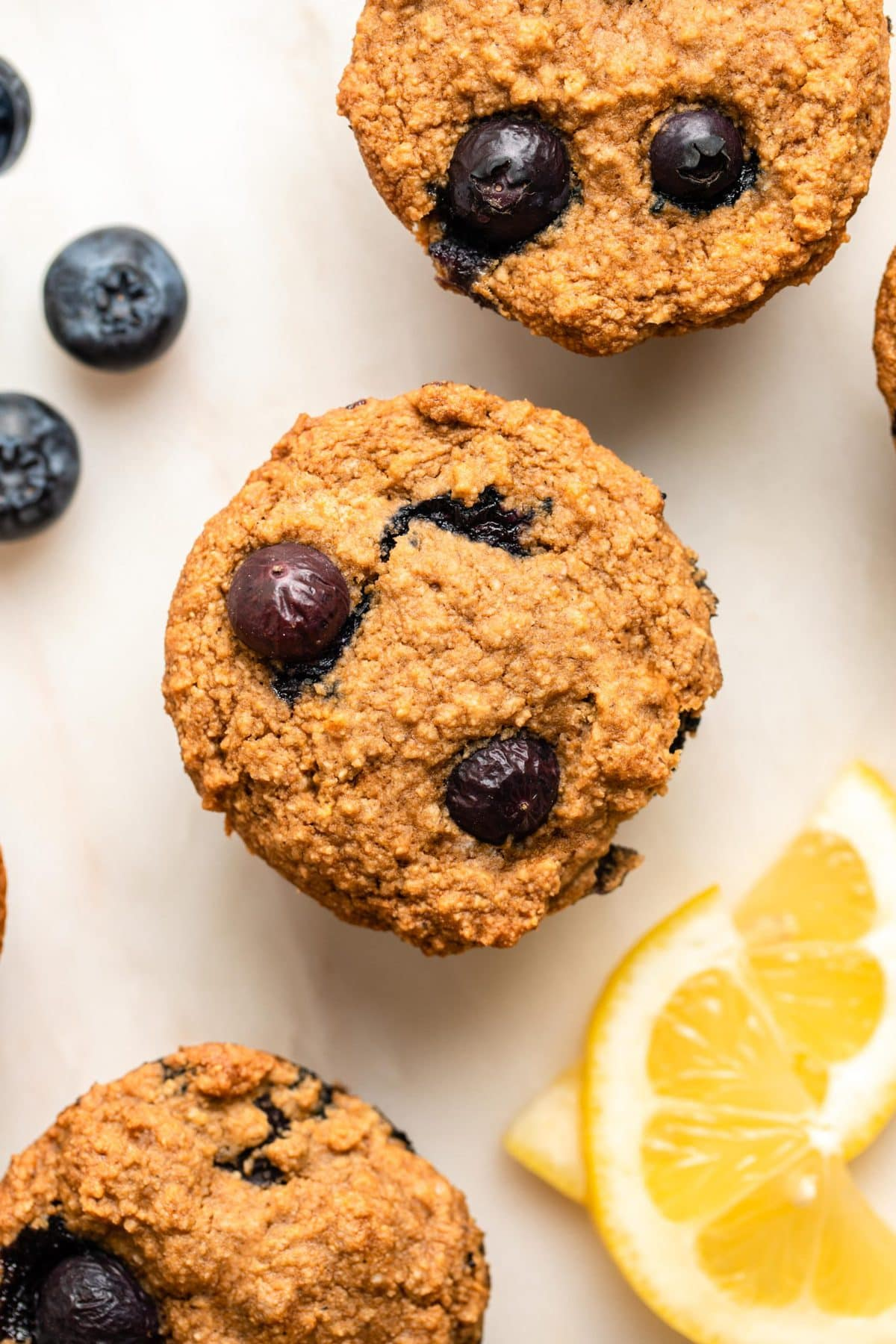 close up photo of tops of 3 lemon blueberry muffins on white background