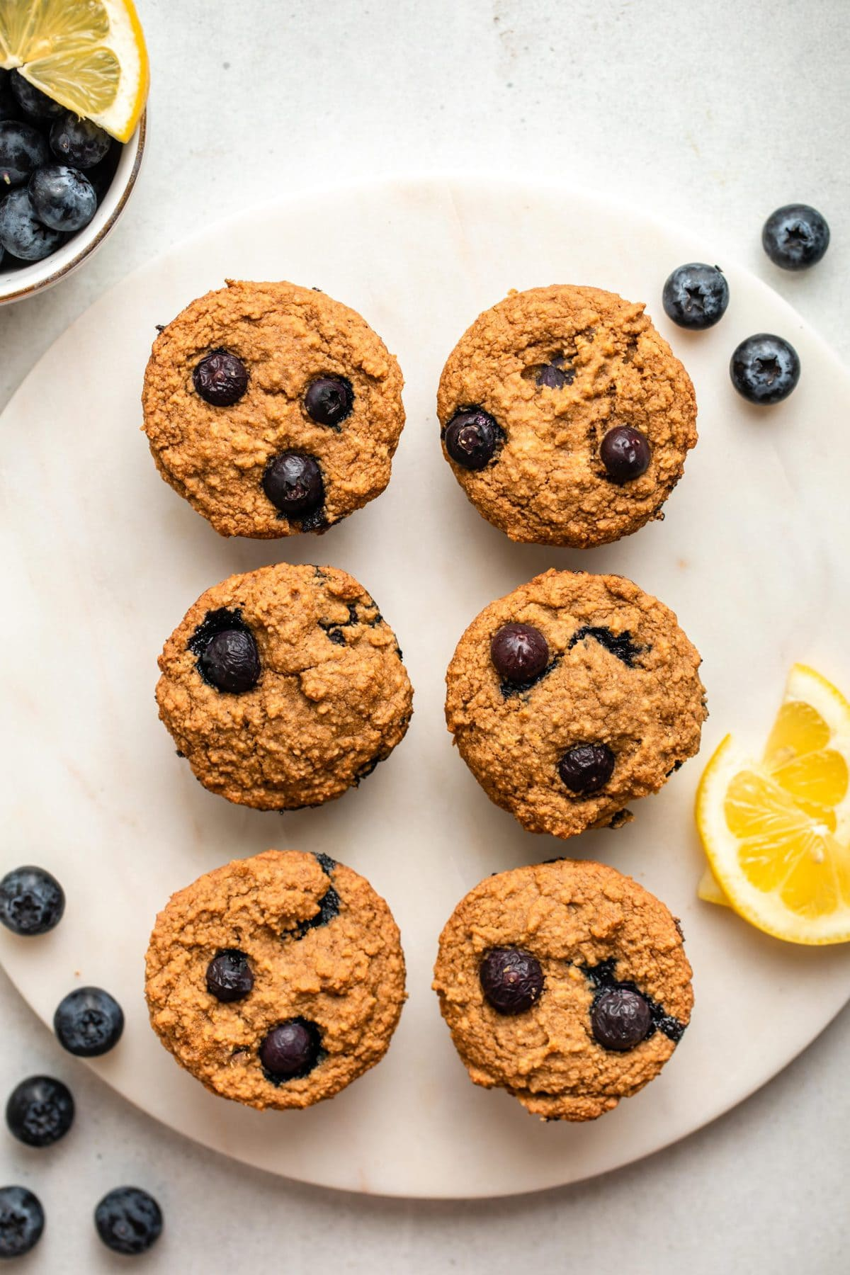 six lemon blueberry muffins on white serving tray with lemon slices and fresh blueberries