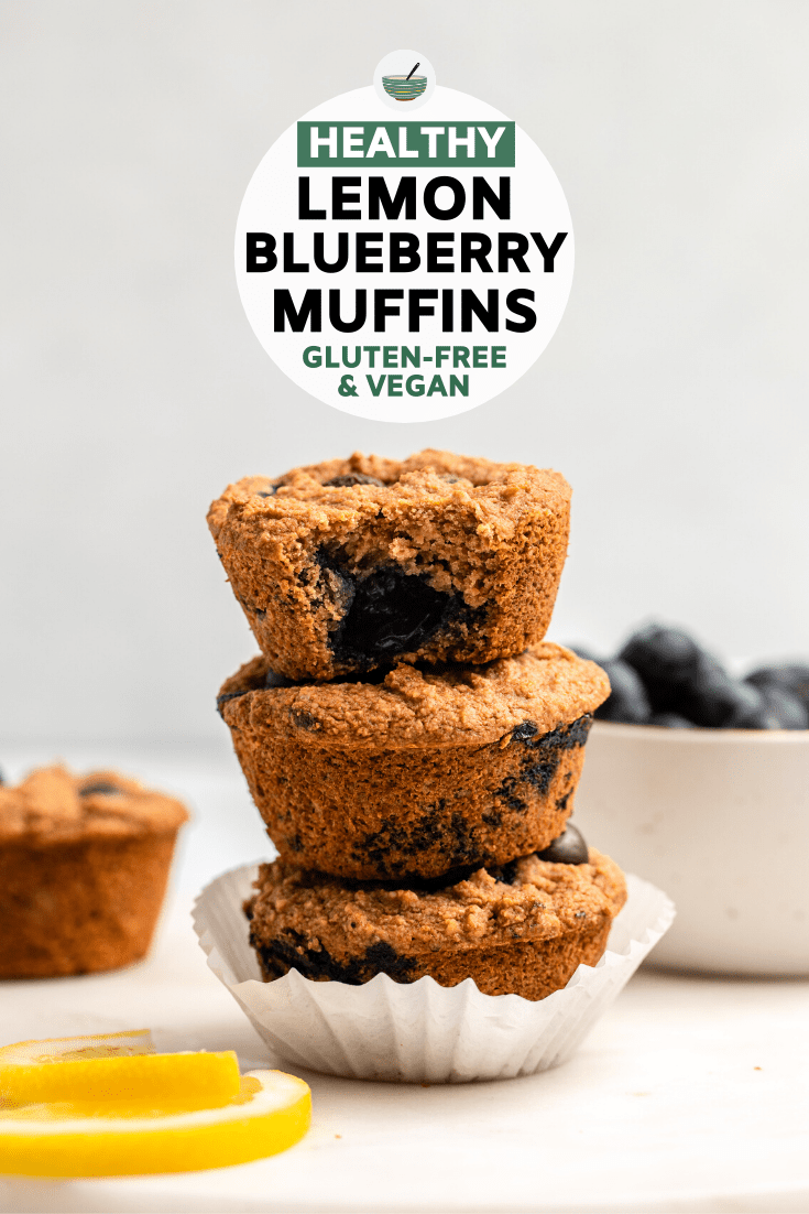 stack of lemon blueberry muffins with lemon slices and blueberries against white background