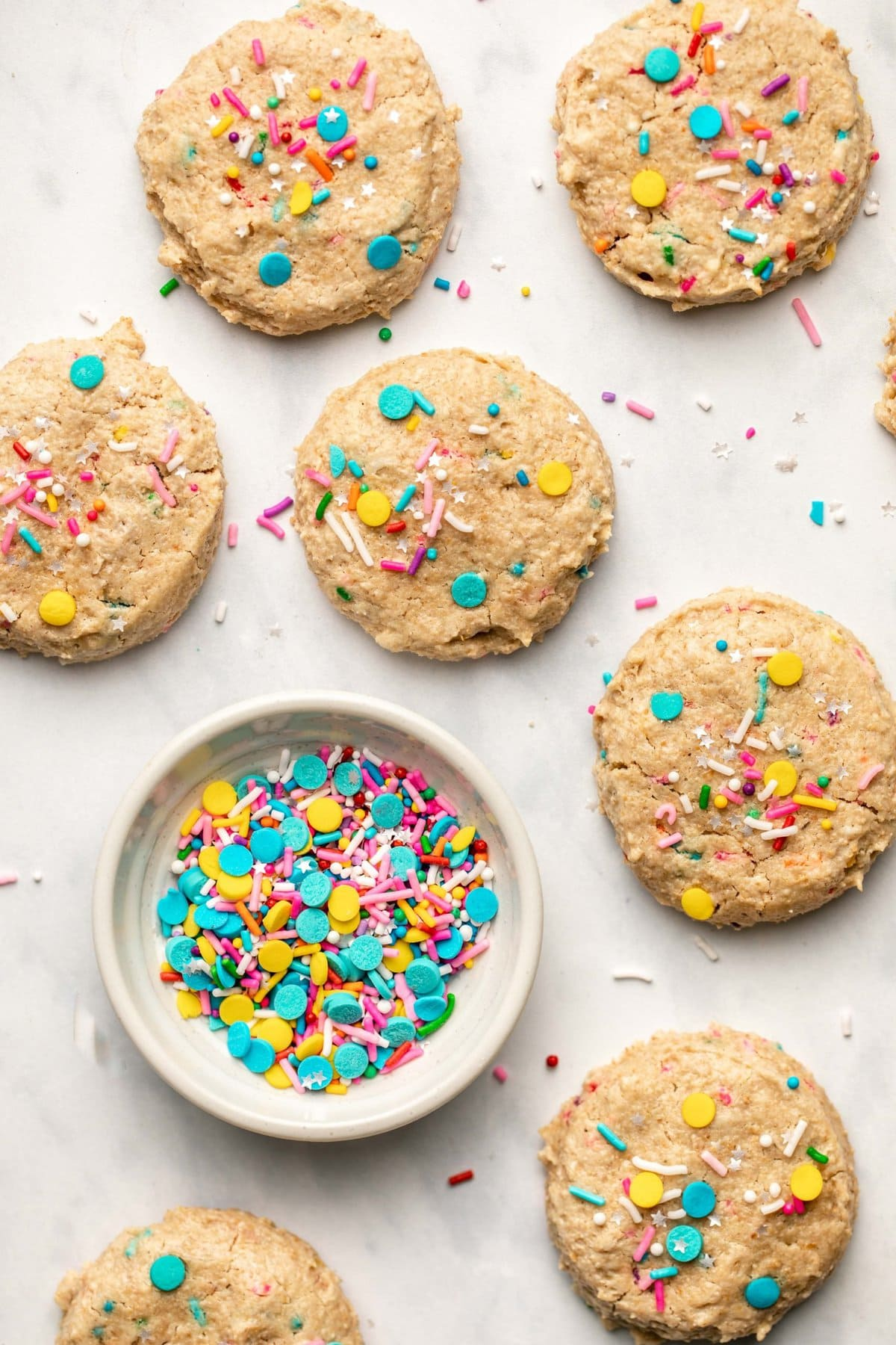 funfetti cookies on marble background with bowl of sprinkles
