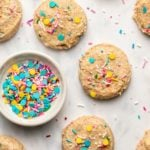 soft baked vegan funfetti cookies on marble background with small bowl of sprinkles