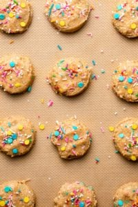 unbaked funfetti cookies on lined baking tray topped with sprinkles
