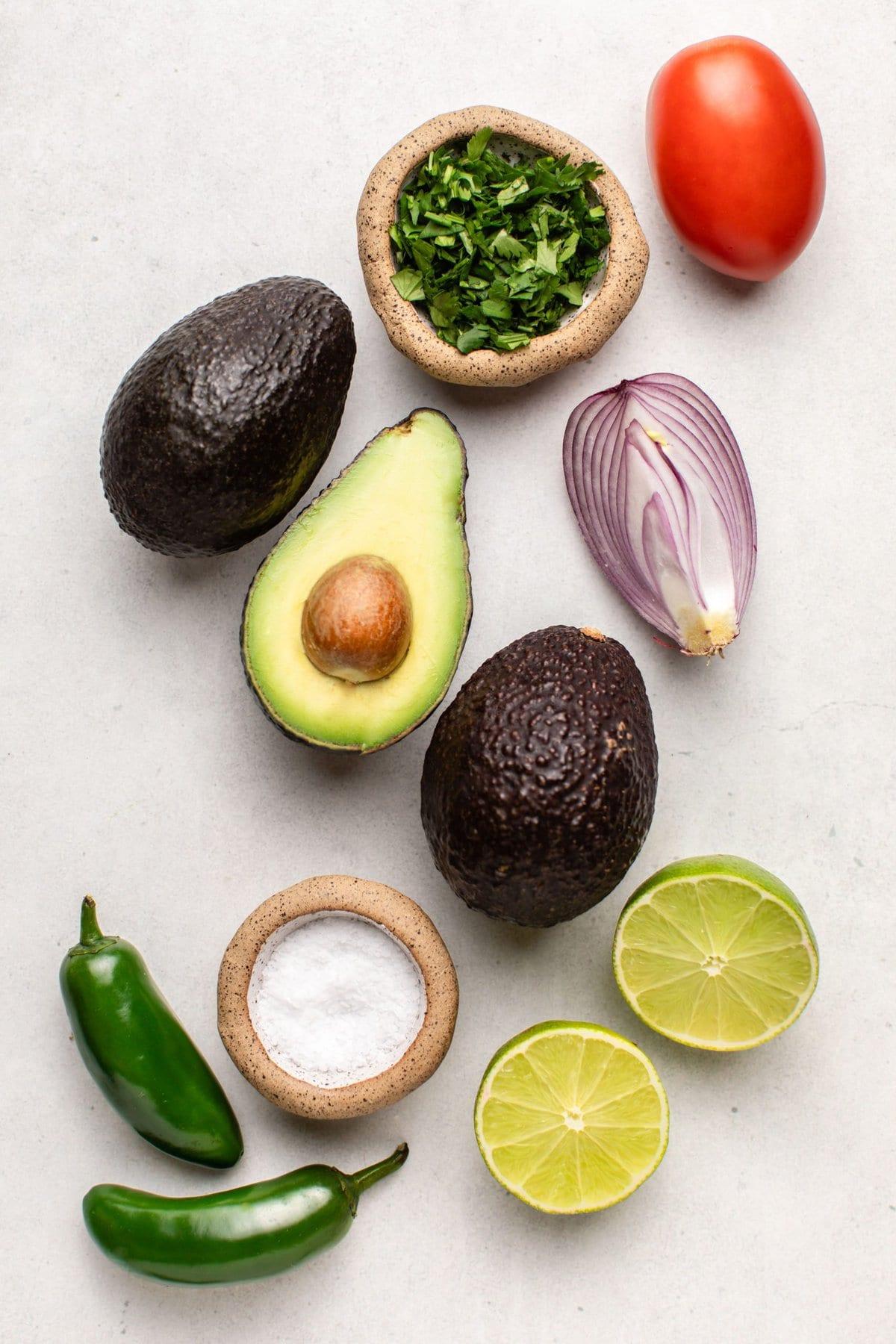 avocados, tomato, cilantro, jalapeno, lime, salt, and red onion on white background