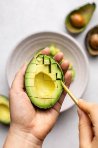 scooping scored avocado with spoon