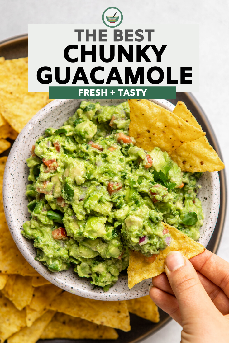 hand dunking tortilla chip into white bowl of guacamole