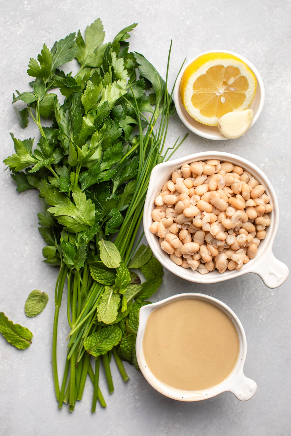 ingredients for creamy white bean dip in small white bowls on grey background
