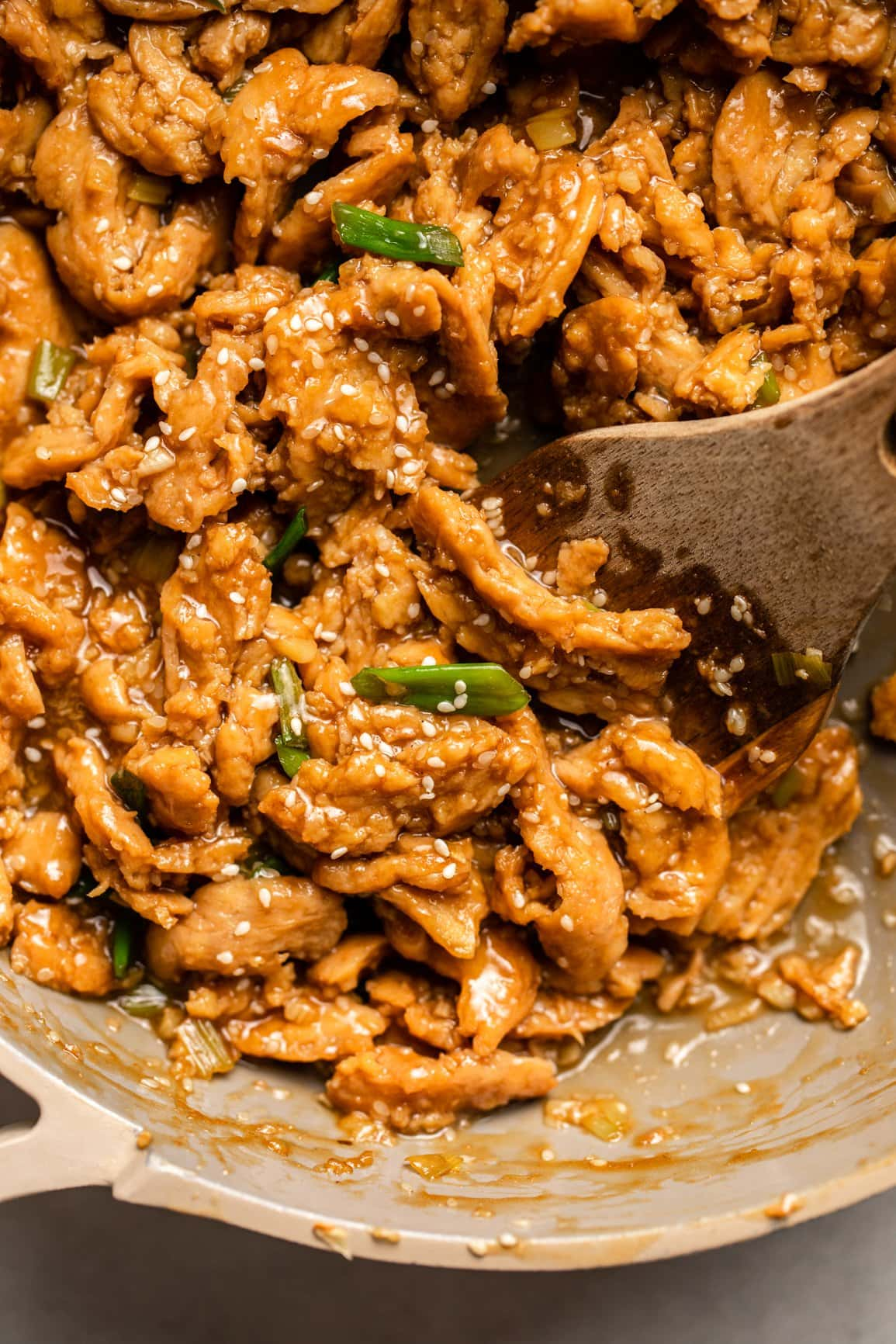 cooked vegan sesame chicken in tan skillet topped with green onions