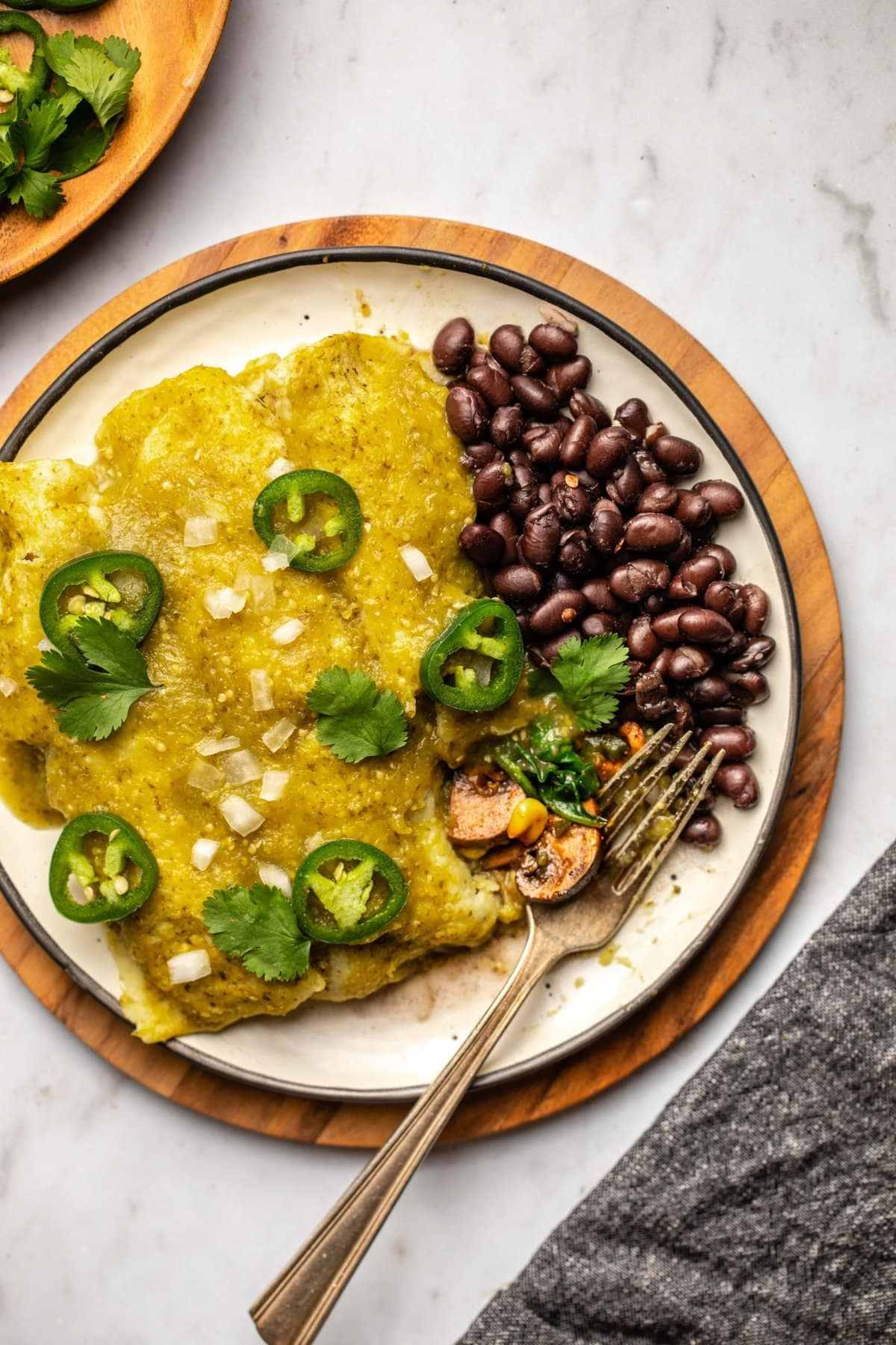 spinach and mushroom enchiladas with salsa verde and black beans on plate