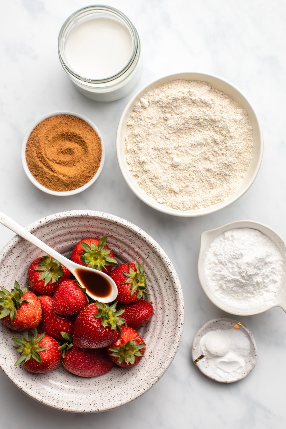 ingredients for strawberry upside down cake in white bowls on marble background