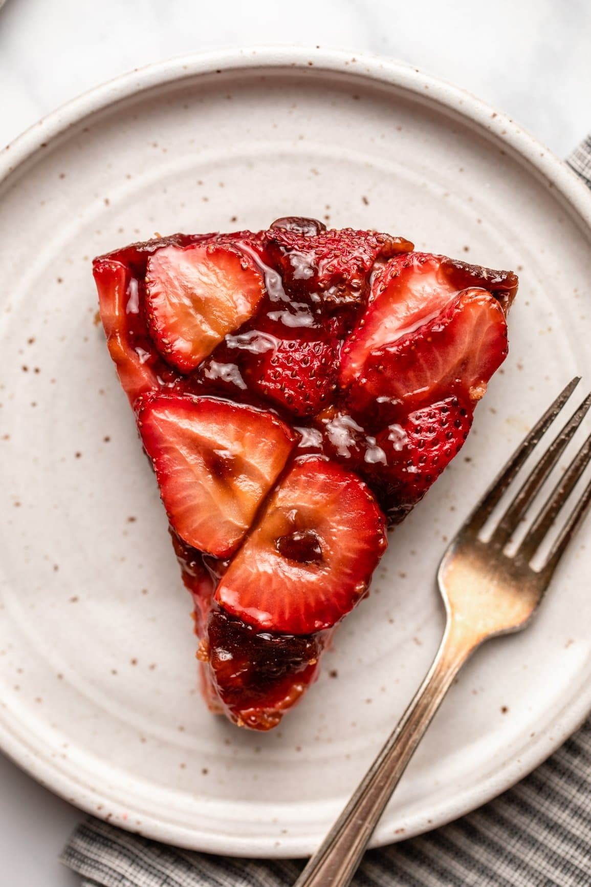 close up photo of slice of strawberry upside down cake on white plate with fork
