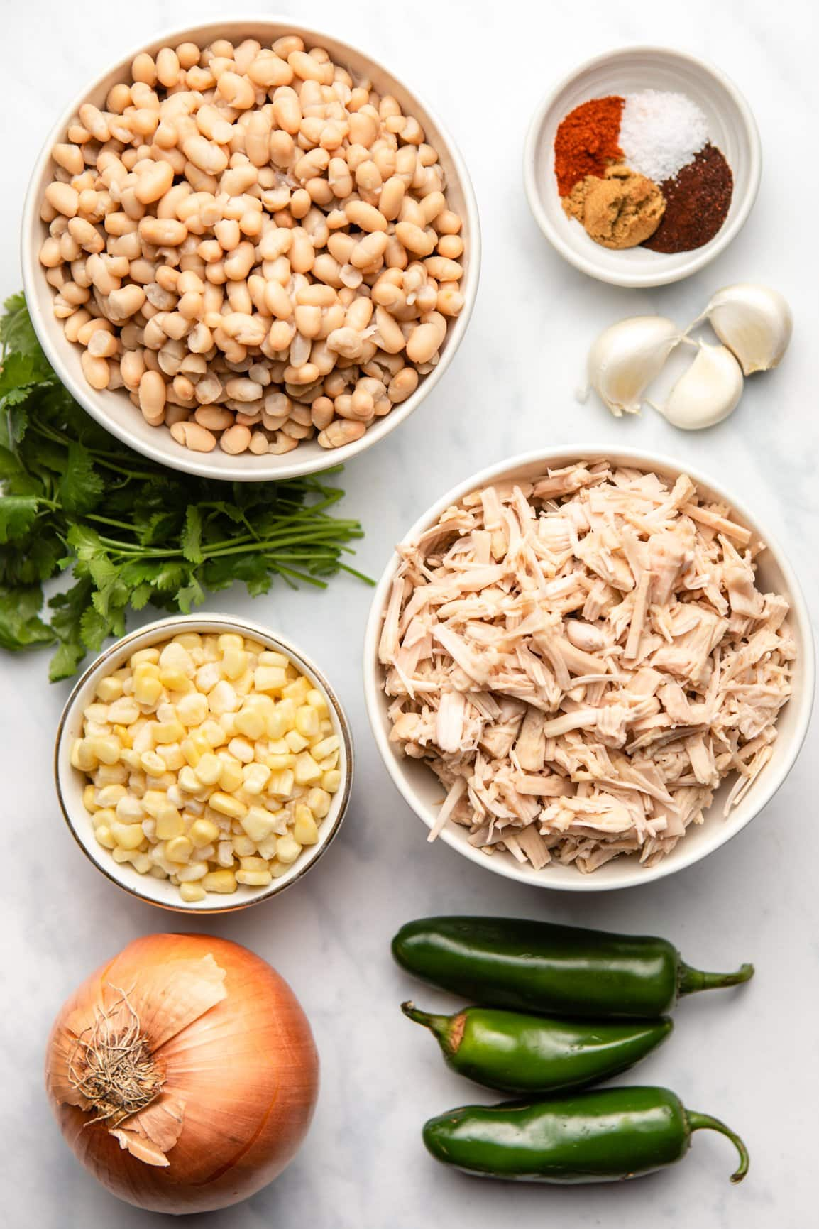 ingredients for vegan white bean chili in small bowls on marble background