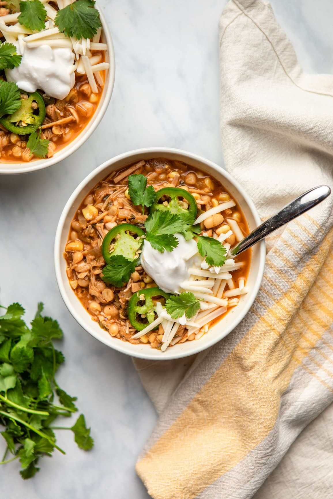 two bowls of vegan white bean chili topped with jalapeno, cilantro, and vegan cheese