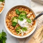 bowl of white bean jackfruit chili topped with jalapeno, cilantro, vegan cheese, and sour cream