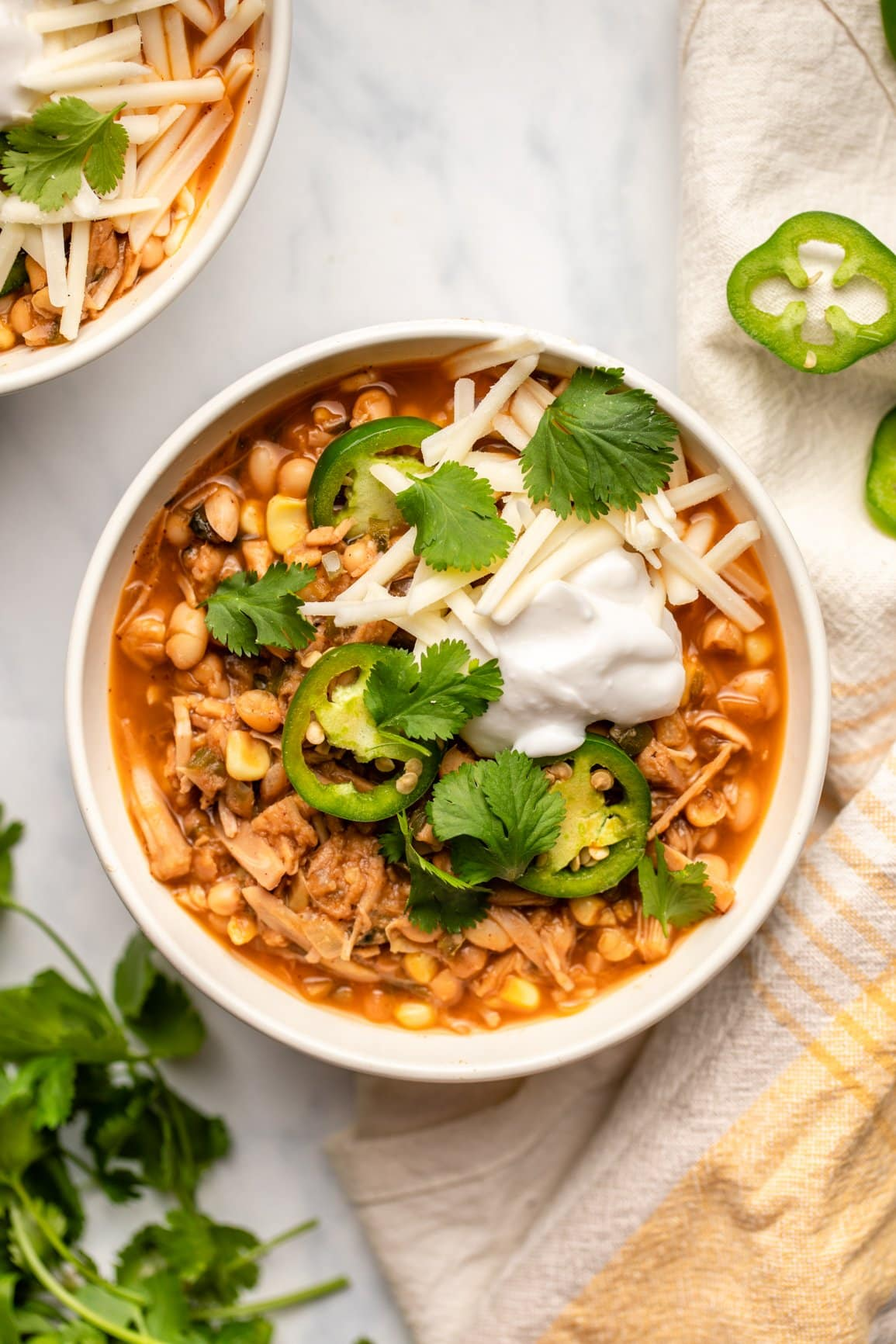 bowl of vegan white bean chili topped with jalapeno, vegan cheese, and vegan sour cream