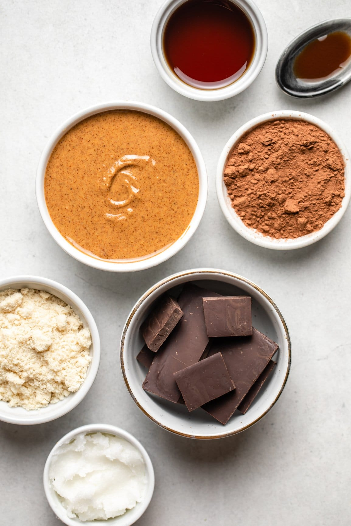 ingredients for chocolate almond butter bars in small white bowls on stone background