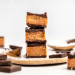 stack of 3 no bake chocolate almond butter bars on white plate with chocolate and almond butter in background
