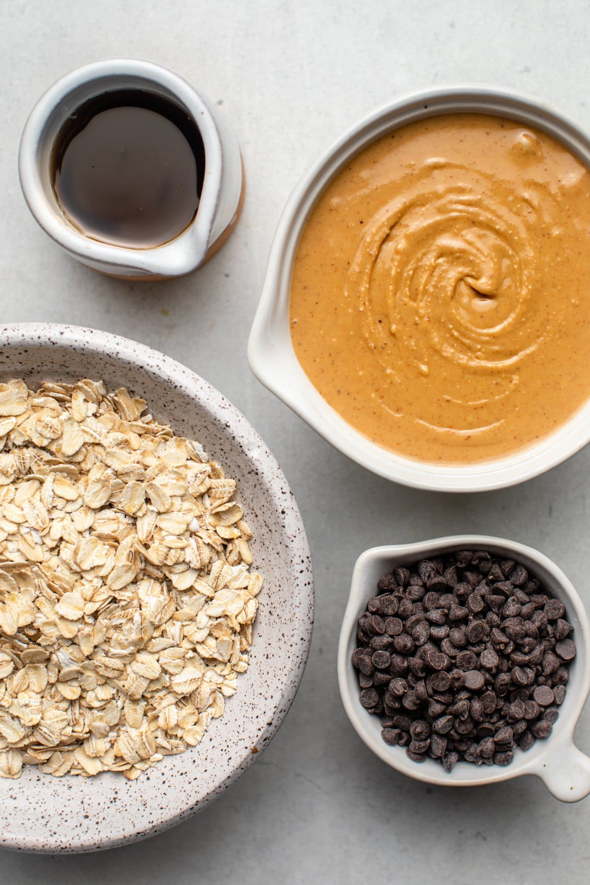 ingredients for peanut butter energy bites in white bowls on white background