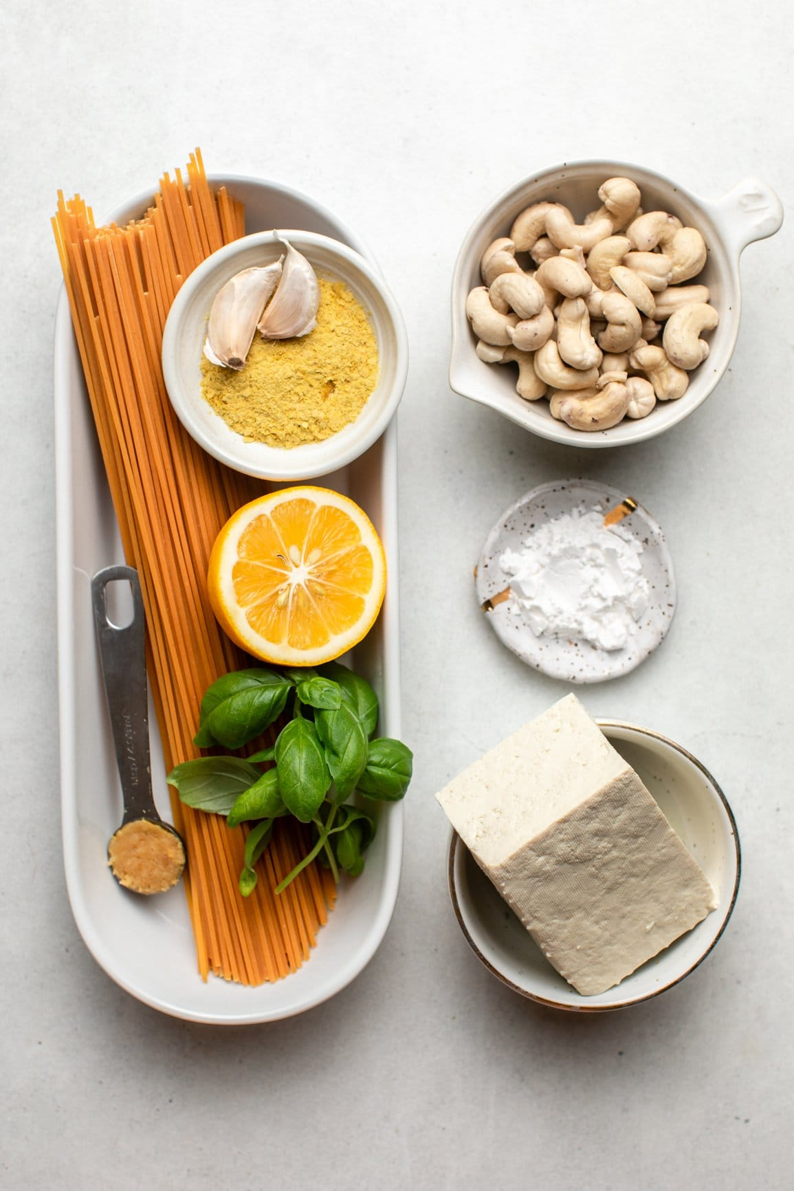 ingredients for lemon ricotta pasta in small white bowls on stone background