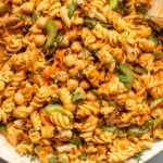 large serving bowl of buffalo cauliflower pasta salad with two wood serving spoons