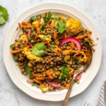 curried lentil salad on white plate and marble background
