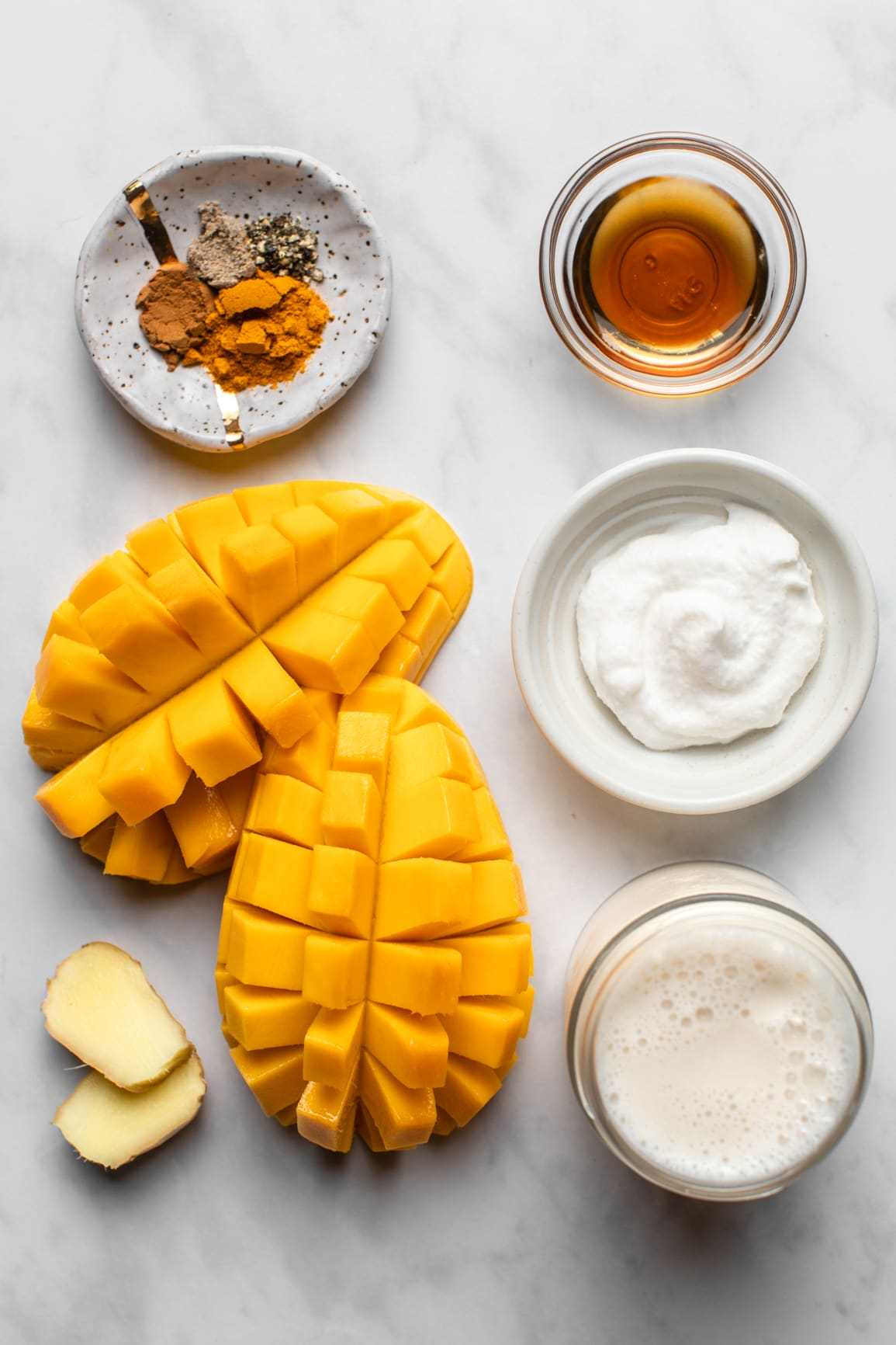 ingredients for golden milk mango smoothie organized on marble background