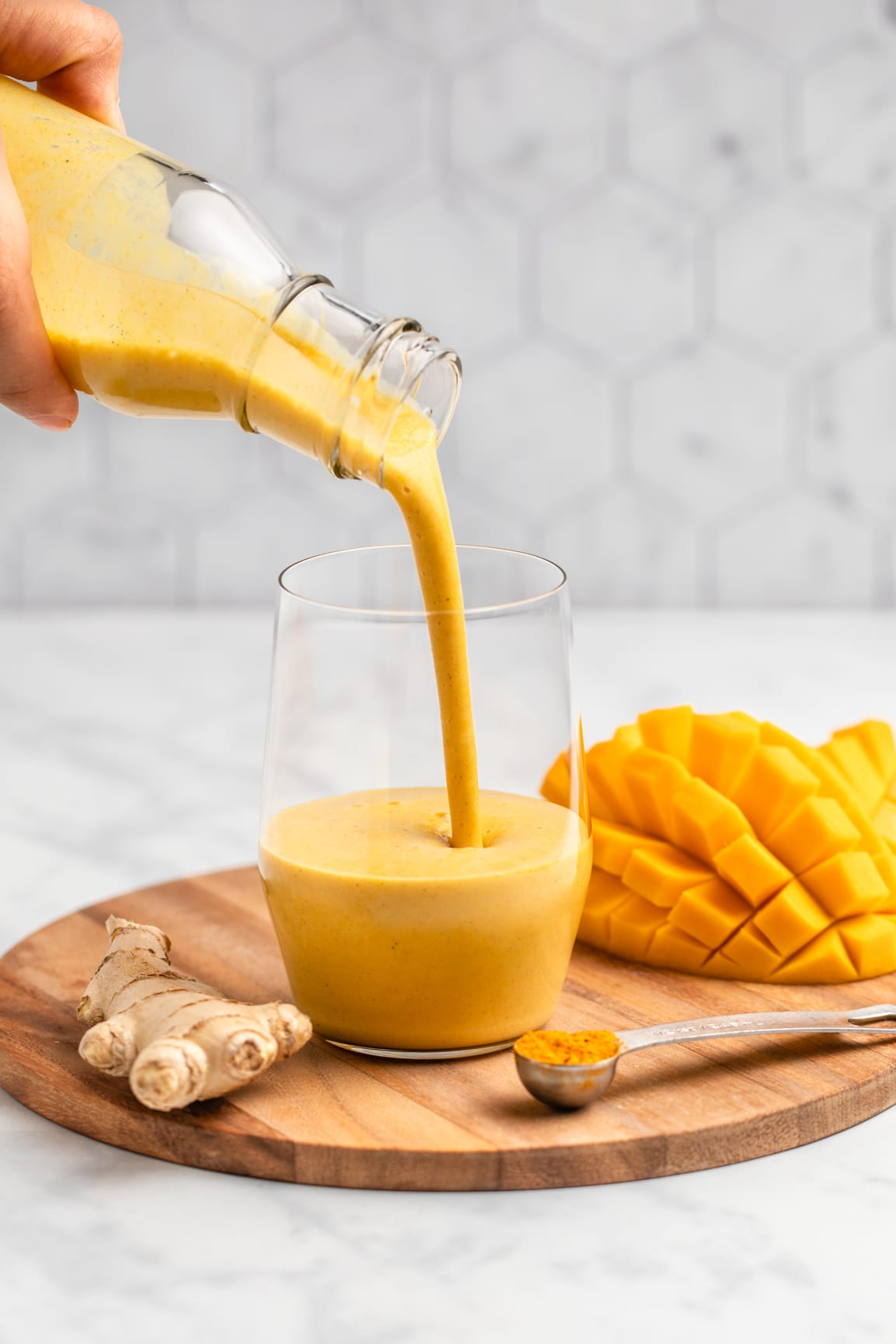 hand pouring golden milk mango smoothie into empty glass on wood serving board