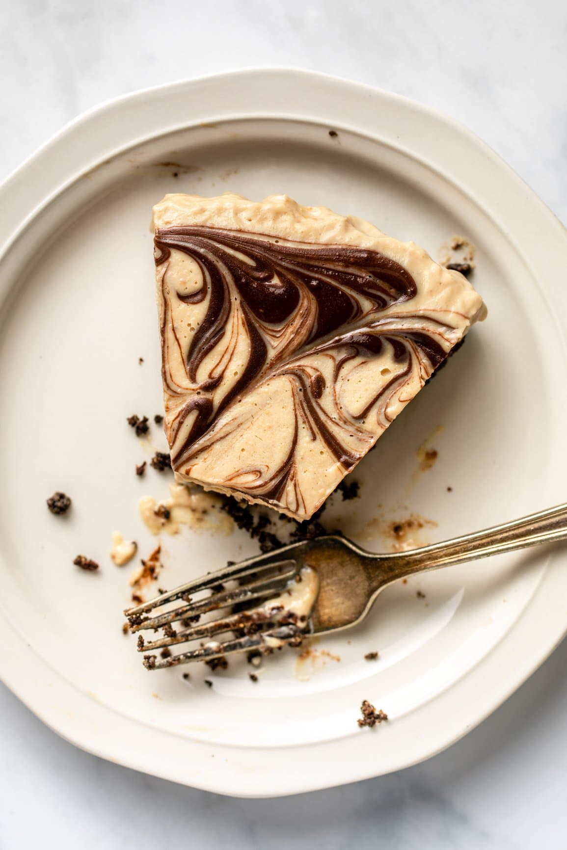 no-bake chocolate peanut butter pie on white plate with bite taken out of it