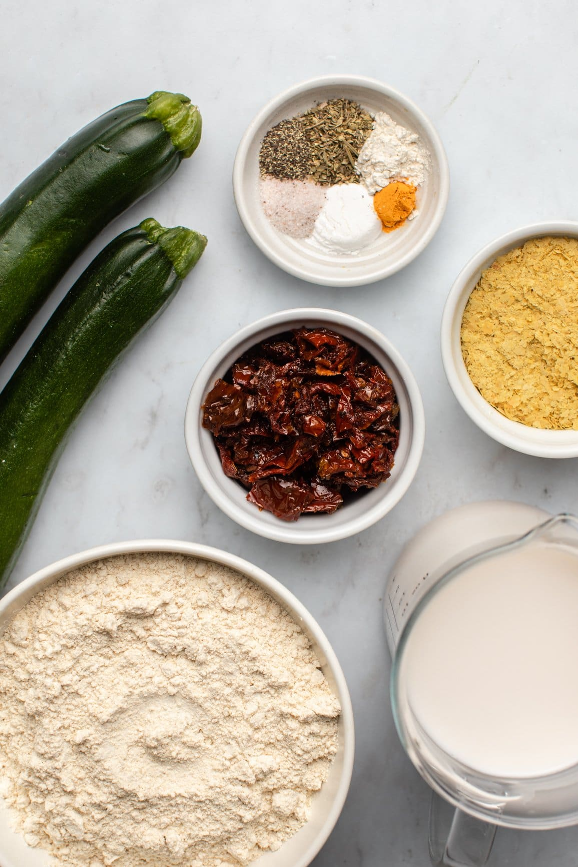 ingredients for savory zucchini muffins in small white bowls on marble background