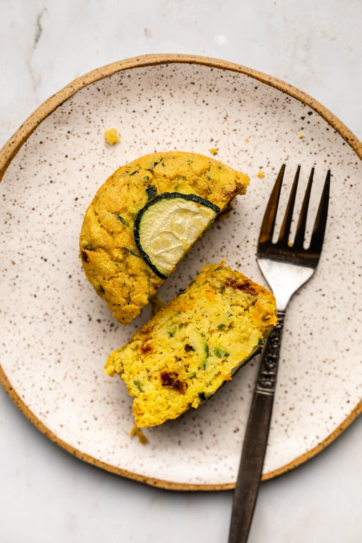 savory zucchini muffin cut in half on white plate with fork