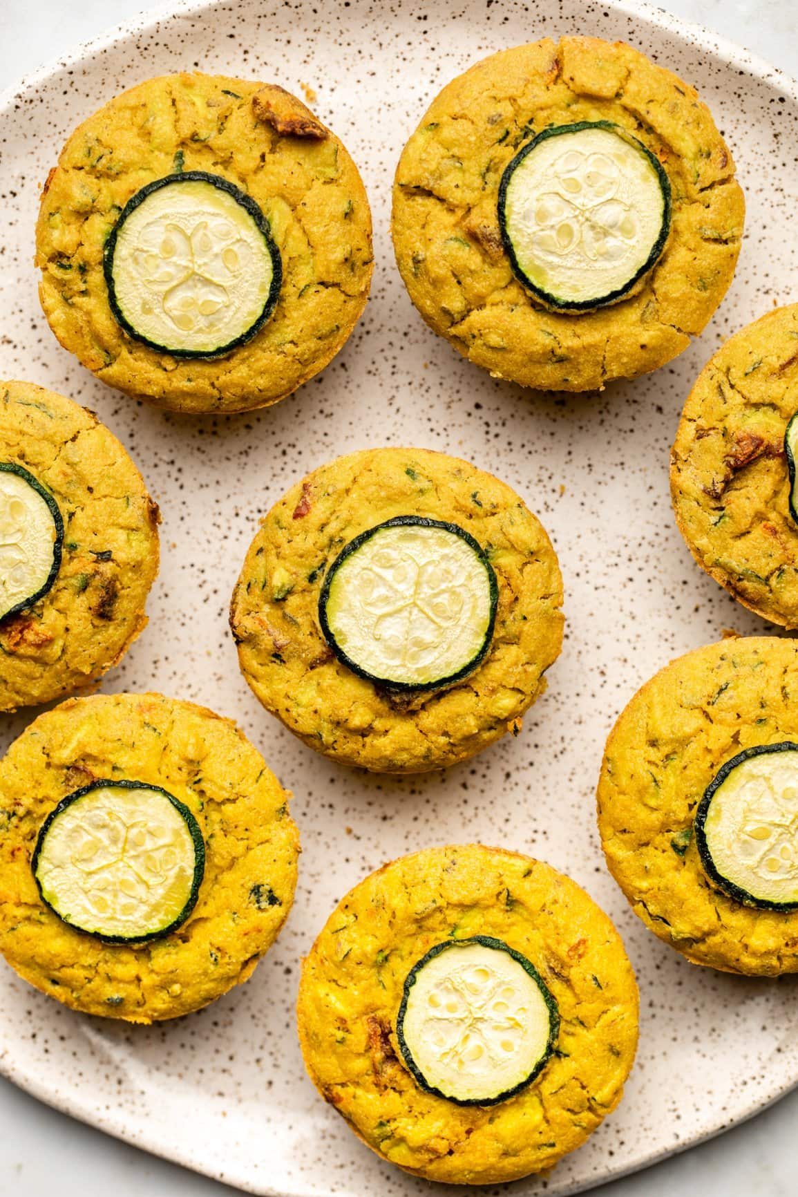 cooked savory zucchini muffins arranged on white speckled plate