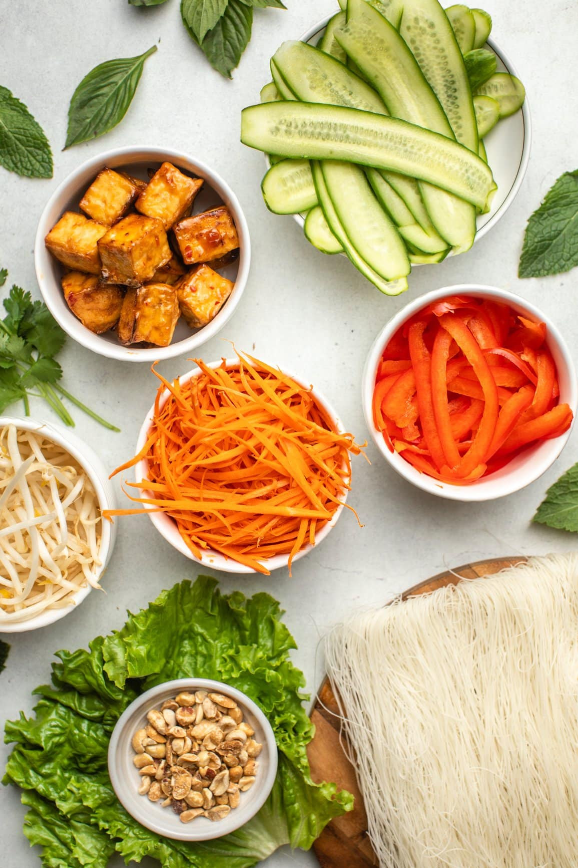 ingredients for vemicelli noodle bowls in small white bowls arranged on marble countertop