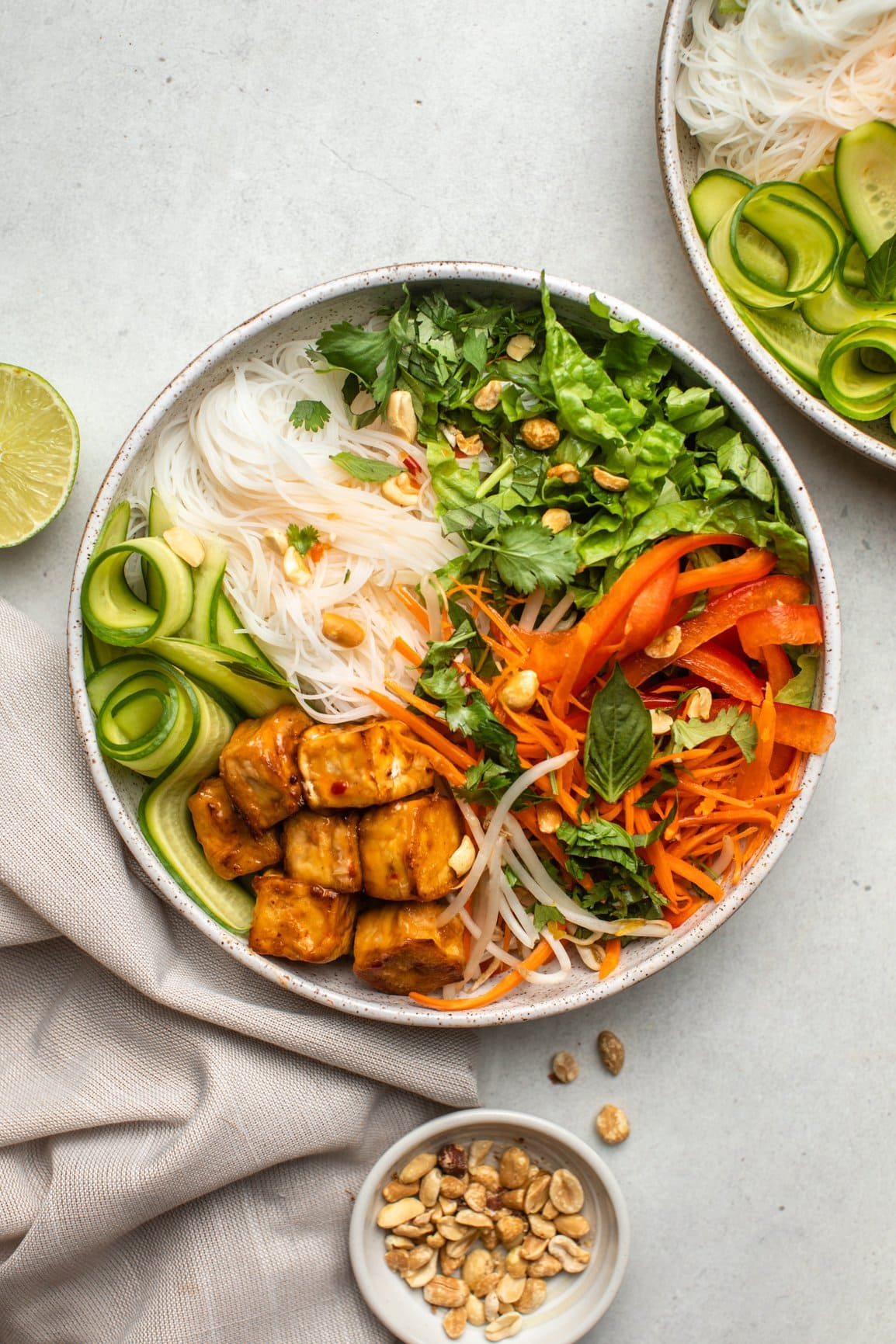vermicelli noodle bowl with fresh lime and peanuts in small bowls on the side