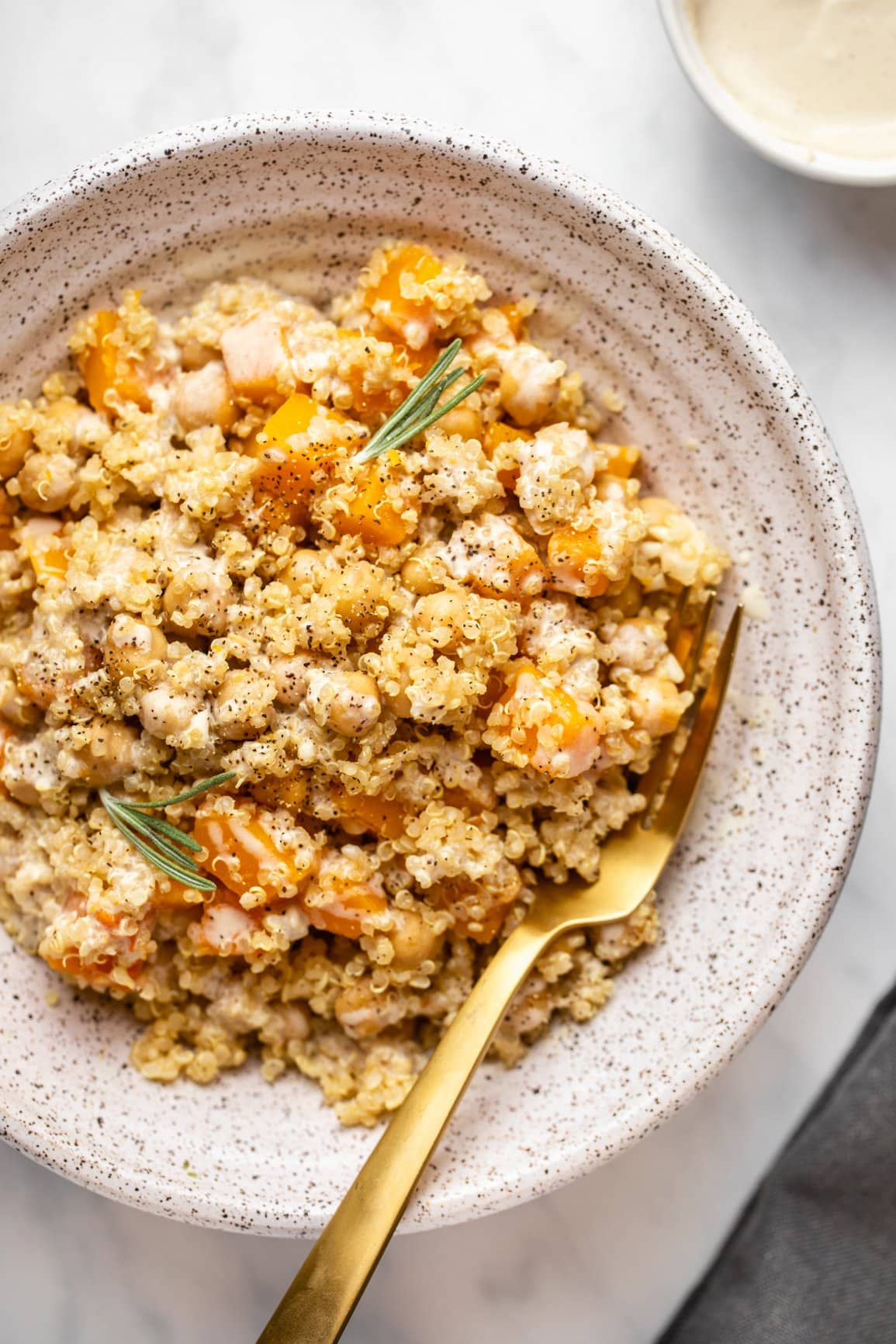 one pot quinoa with butternut squash in white bowl drizzled with tahini