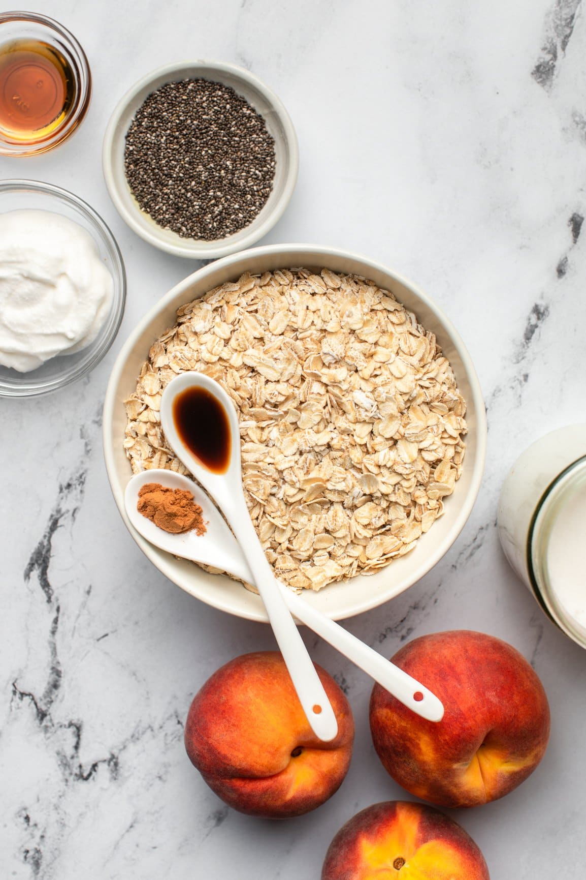 ingredients for peaches and cream oatmeal arranged on marble table top