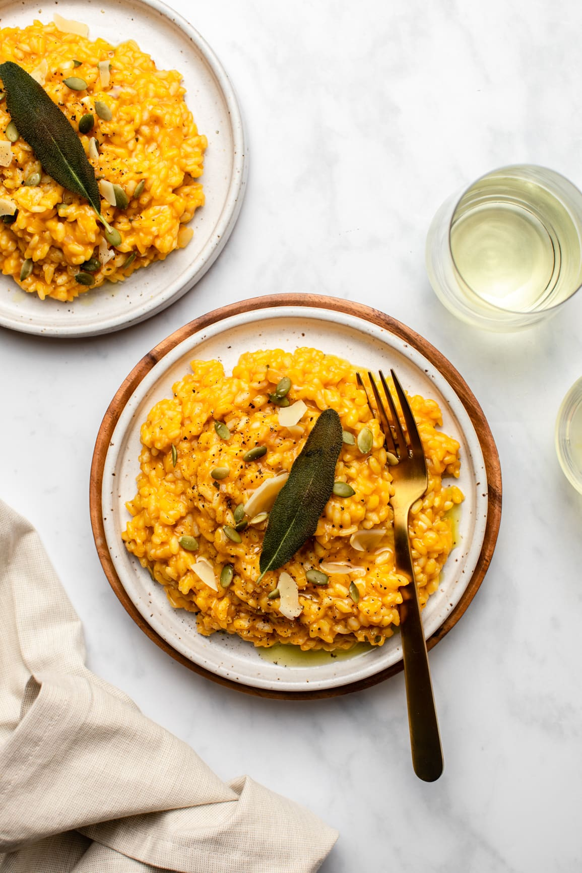 two plates of pumpkin risotto on marble background topped with fried sage alongside glasses of white wine