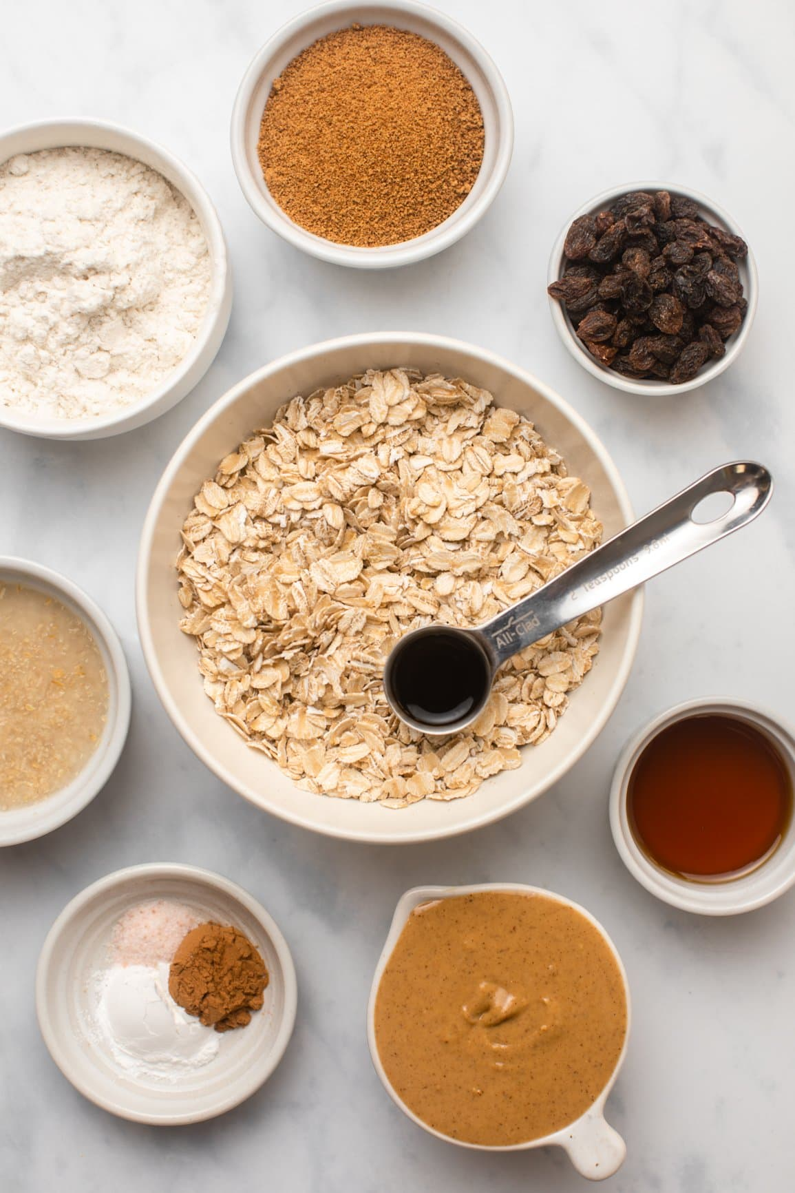 ingredients for cinnamon raisin oatmeal cookies in small white bowls on marble backgrounds