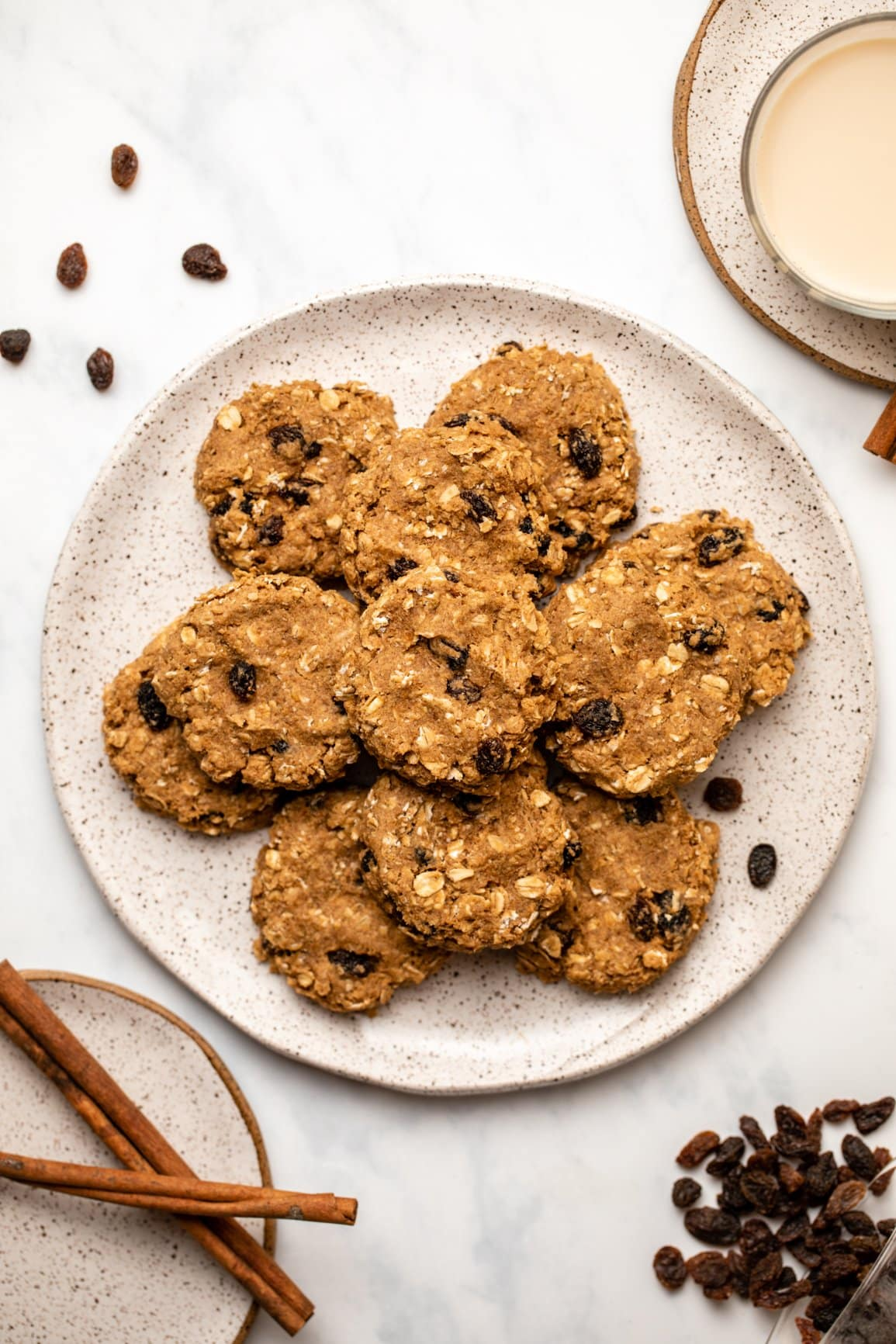plate of cinnamon raisin oatmeal cookies on marble background next to cinnamon sticks and glass of milk
