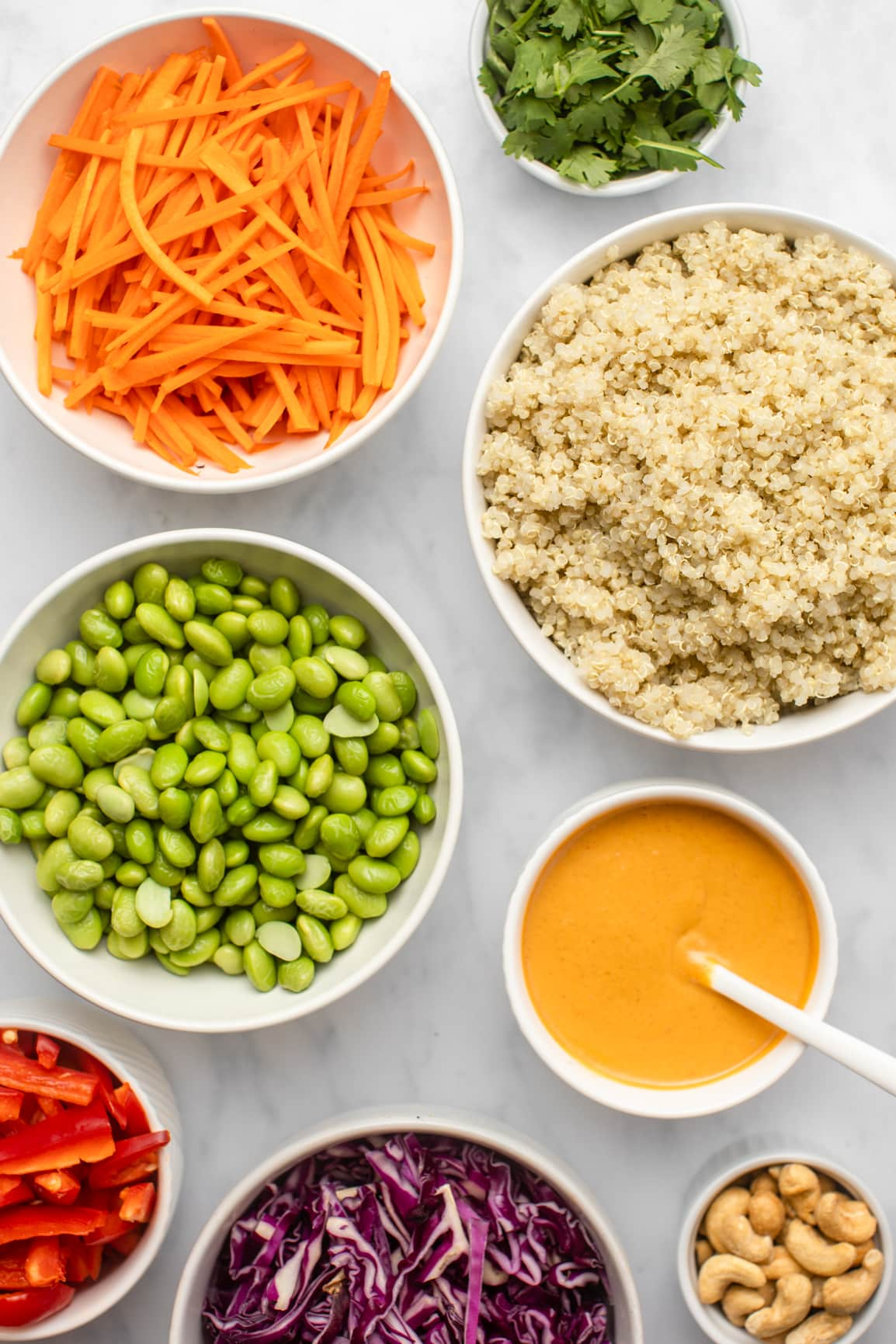 ingredients for rainbow quinoa salad in small white bowls on marble background