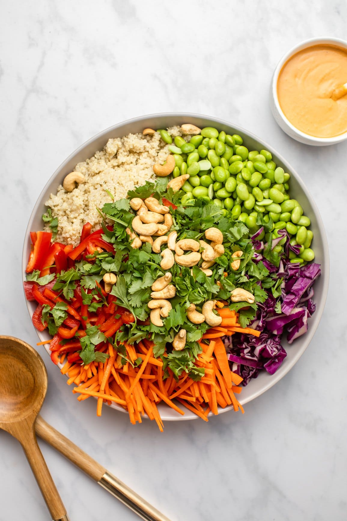 ingredients for rainbow quinoa salad organized in large serving bowl before mixing together with dressing on the side