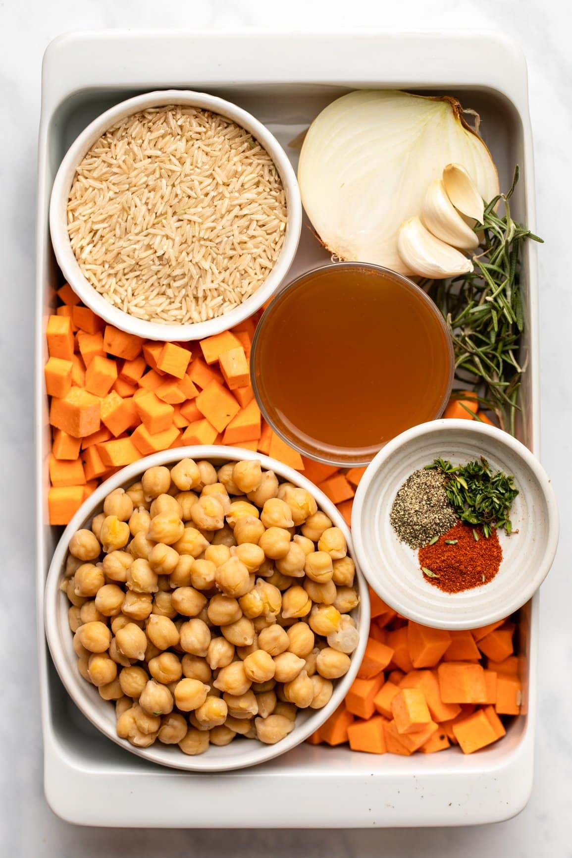 ingredients for sweet potato rosemary casserole arranged inside of casserole dish in small white dishes
