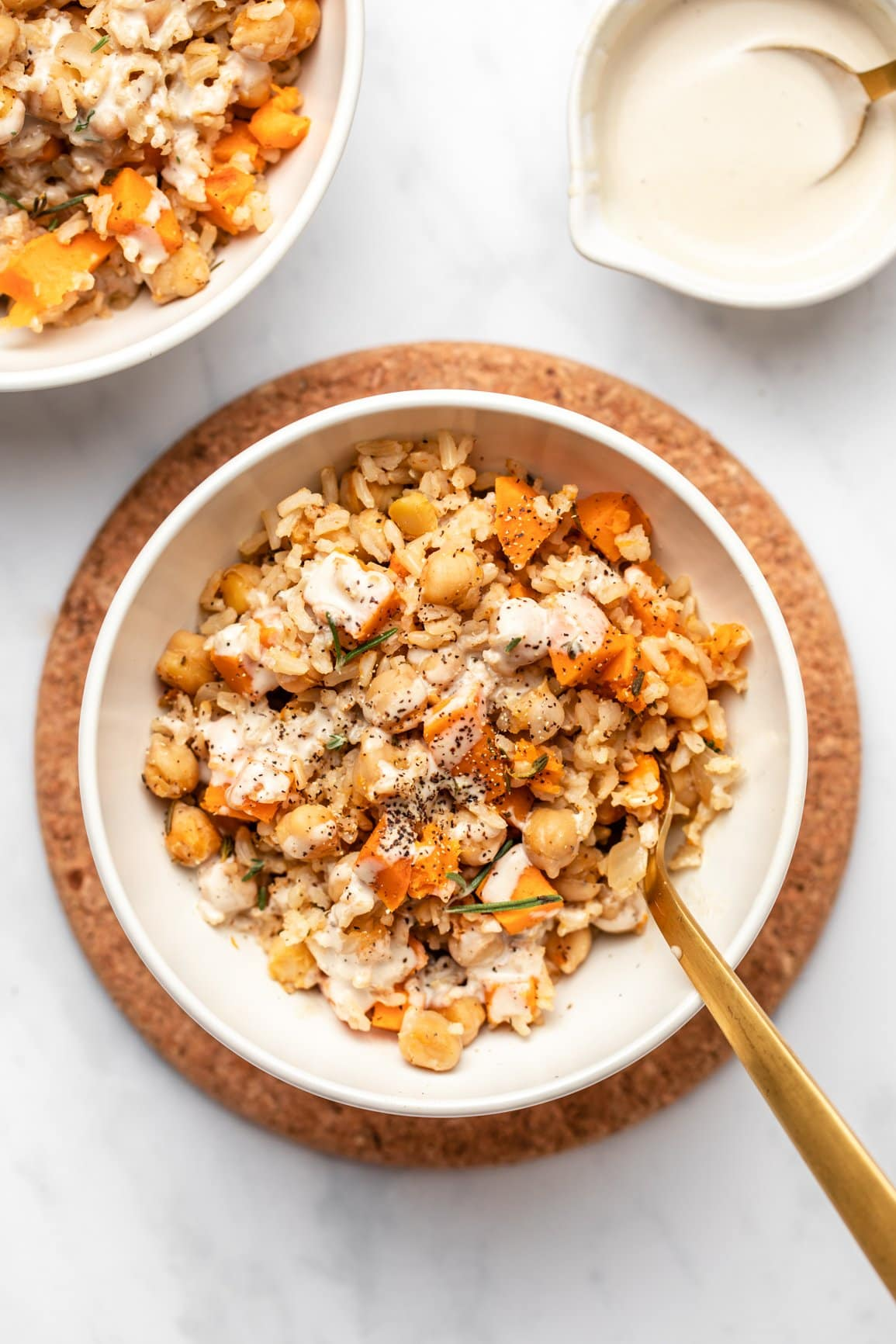 sweet potato rosemary casserole in white serving bowl topped with tahini dressing and black pepper
