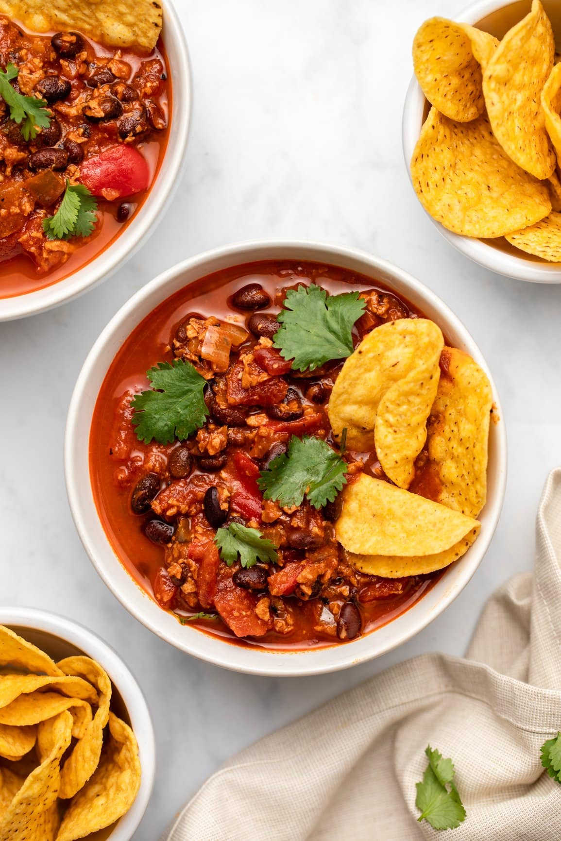 two bowls of chorizo chili with tortilla chips on the side